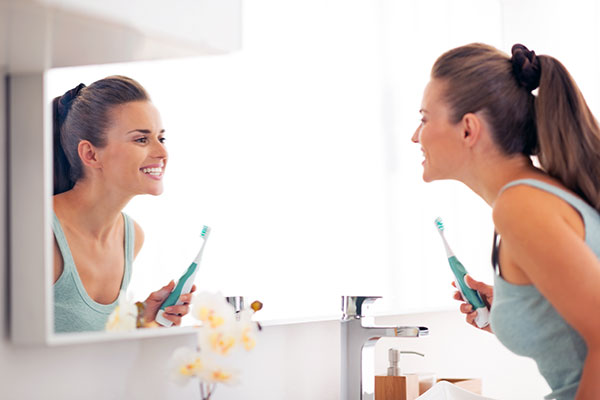woman brushing teeth to prevent gum inflammation